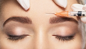 a person receiving a BOTOX injection between their eyebrows