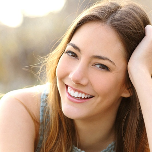 A young female smiling wide to show off her whiter teeth thanks to teeth whitening in Brick Township