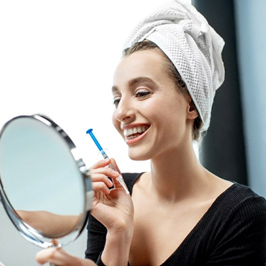 A young woman with a towel on her head, holding a syringe with whitening gel and a hand-held mirror to look at her brighter smile